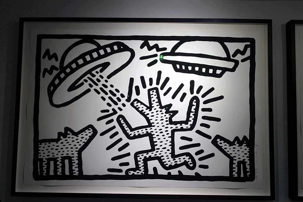 RHODES Contemporary Art Gallery..>Haring developed an early love for drawing, partly taught by his father and taking inspiration from popular culture around him. Despite a brief spell training to be a commercial graphic artist, Haring truly honed his skill upon moving to New York and becoming a core part of the alternative art community of the era. He was often found organising events at Club 57 and hanging out with such idols of the era as Jean-Michel Basquiat and Madonna.